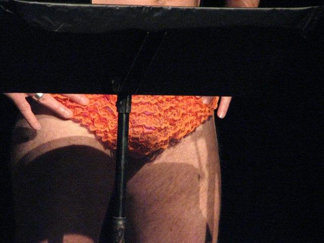 Close up shot of a crotch with orange ruffled panties