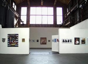 Wide angle image of a gallery with white walls and photographs