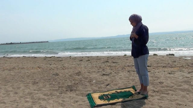 photo of woman stanging in front of prayer rug on a beach