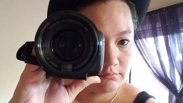 woman looking through camera lens