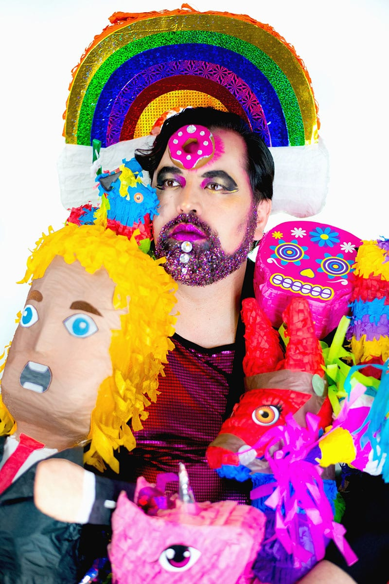 Person with dark hair and beard with pink lipstick surrounded by pinatas with a rainbow behind their head