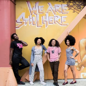 Group of black and brown people standing in front of a grafitti that says we are still here