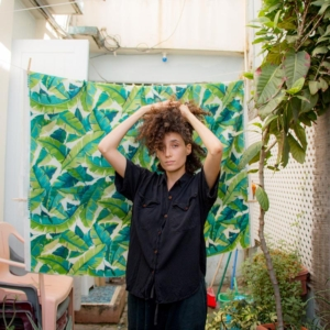 Brown curly haired person holding their hair up in black short sleeved jumpsuit standing against backdrop of green leaves in an outdoor space